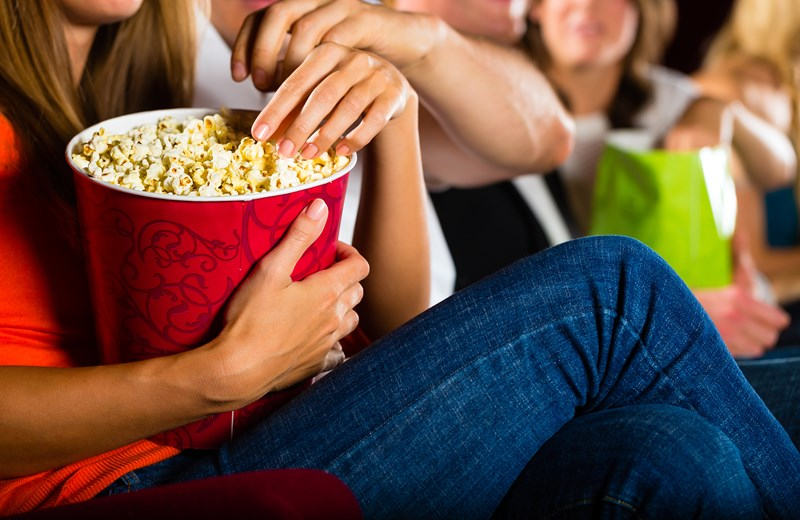 7138592-girl-eating-popcorn-in-cinema-or-movie-theater.jpg