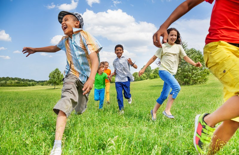 9349051-kids-in-motion-of-running-on-green-field.jpg